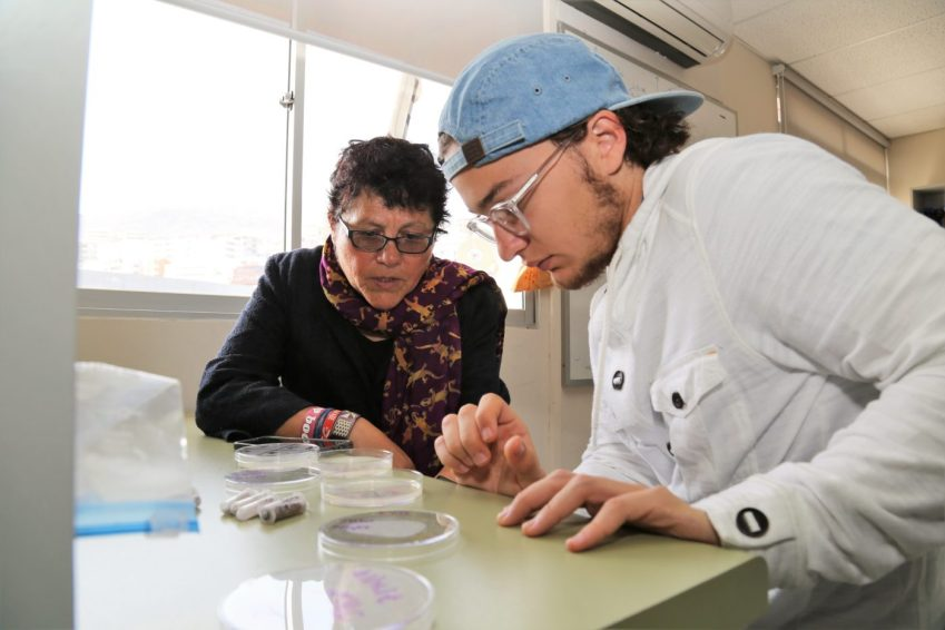 Associate Professor veronica Godoy-Carter and a student look at something in a dish on a bench.