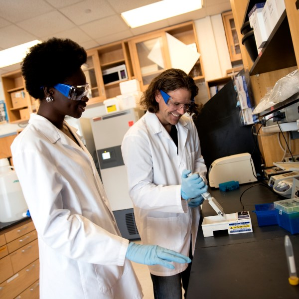 Student Yaa Kyeremateng and Professor James Monaghan work together at a lab bench.
