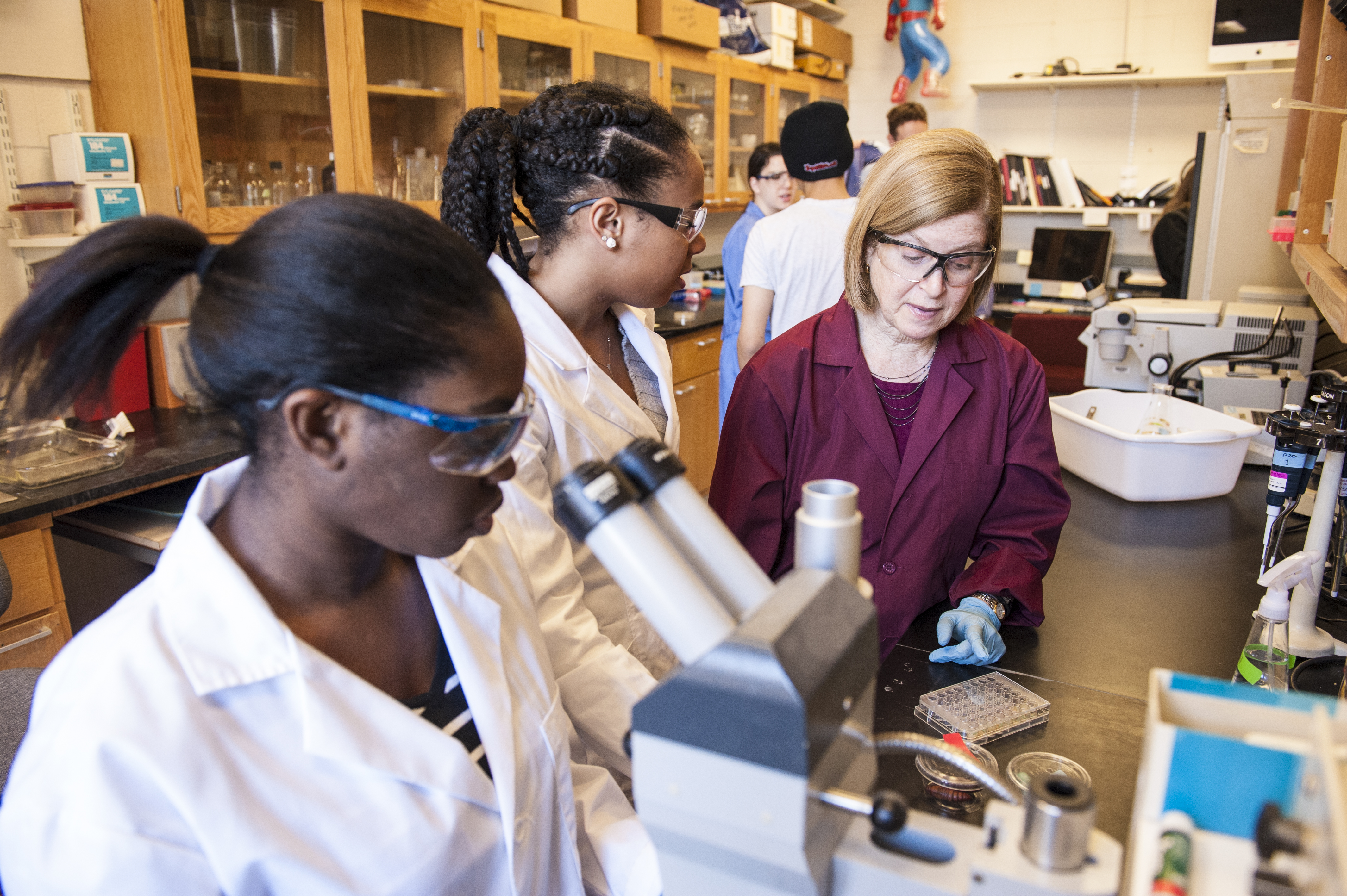 Two female students discuss an experiment in lab with Professor Wendy Smith. The two students and Professor Smith stand at the lab bench near a microscope.