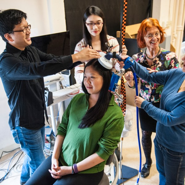 A female student holds a measuring device up to the head of a student test-subject. A male student support the device and two female students stand by and watch. Professor Dagmar Sternad talks to the students.