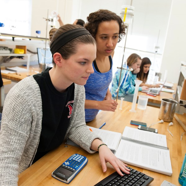 Two female students work on a physics lab. Other groups of students can be seen doing the same experiment in the background.