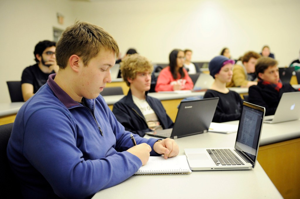 Students sitting in a classroom in front of computers.