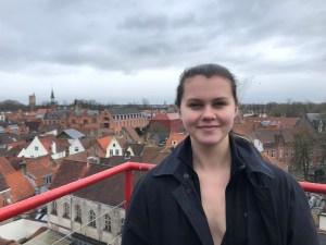 Ella Brunsting standing on a balcony looking over Bruges Belgium