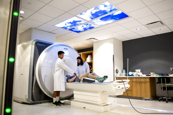 08/06/19 - BOSTON, MA. - Students put headphones on a subject during a MRI test in the Biomedical Imaging Center in the Interdisciplinary Science and Engineering Complex on August 06, 2019. Northeastern researchers Psyche Loui and Ajay Satpute are studying the relationship between musical anhedonia and autism spectrum disorders to identify weaknesses in treatments like music therapy. Photo by Ruby Wallau/Northeastern University