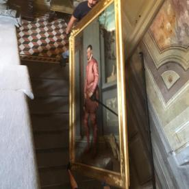 Il quadro del Cavaliere in Rosa scende le scale con due addetti