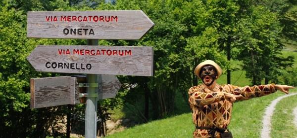 Arlecchino che indica Oneta lungo la via Mercatorum