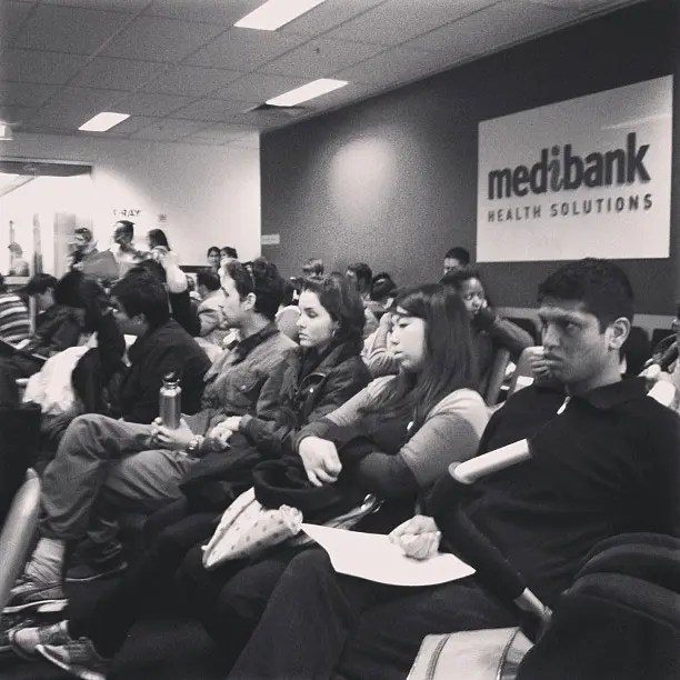 Immigrants in a waiting room waiting to get a medical assessment.