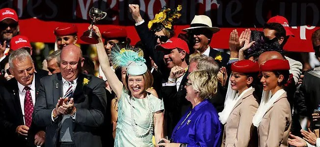 Gai Waterhouse holding up her Melbourne Cup.
