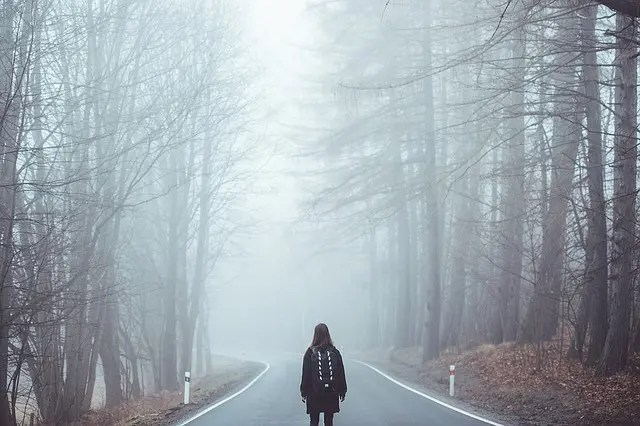 A person on a foggy road. Expat life, wanderers.