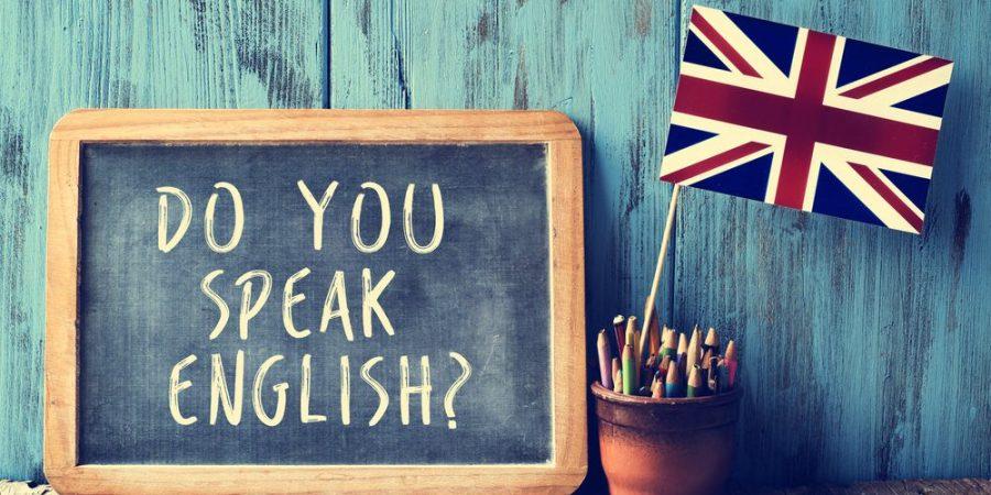 """Blackboard that says, """"Do you speak English? next to the British flag. Australian English."""