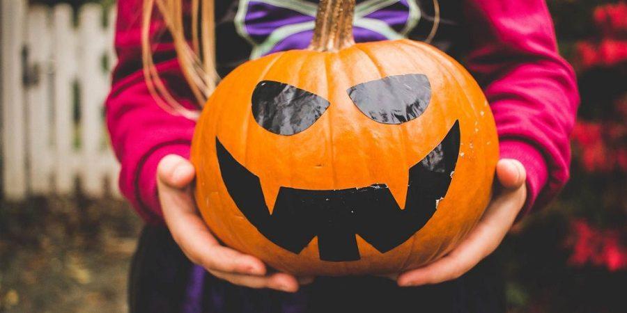 Child holding Halloween pumpkin.