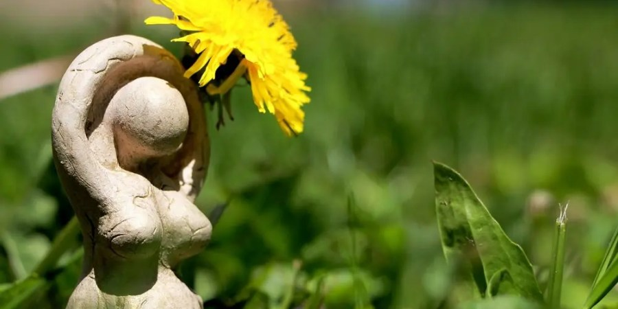Spirituality, paganism. Little statue of a goddess with a flower.