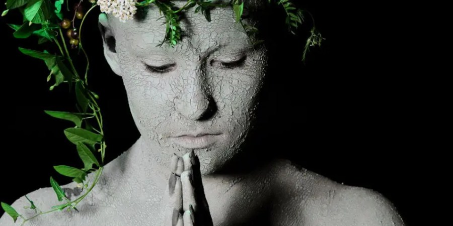 Environment - praying woman covered in mud and wearing flowers