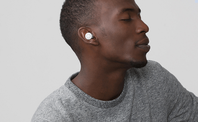 A man wearing Here One wireless earbuds.