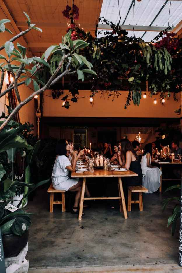 unrecognizable people having banquet at tables in restaurant near plants