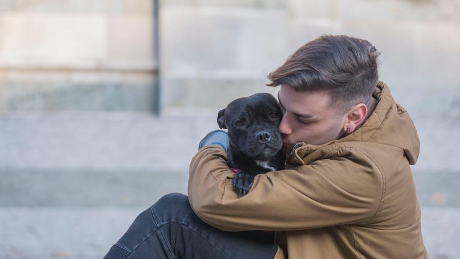 Young man kissing a black puppy