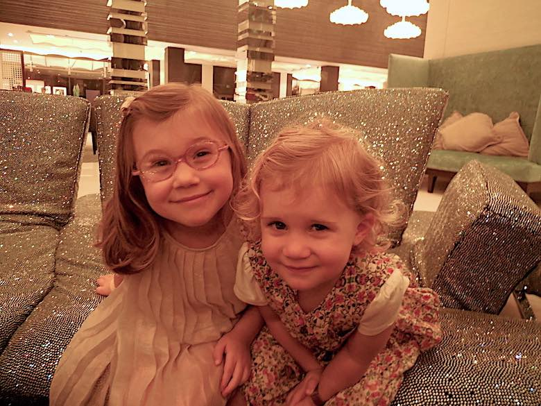 The two CosmopoliClan girls posing for the camera in a sparkling sofa in the lobby of the Fairmont Bab Al Bahr hotel in Abu Dhabi