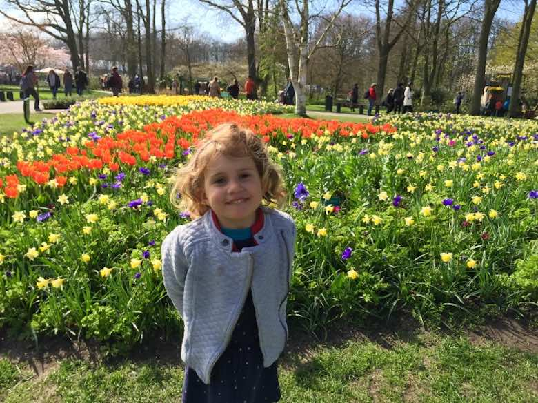 CosmopoliClan girl standing in a field of colorful flowers with a cute expression on her face in Keukenhof Gardens in The Netherlands