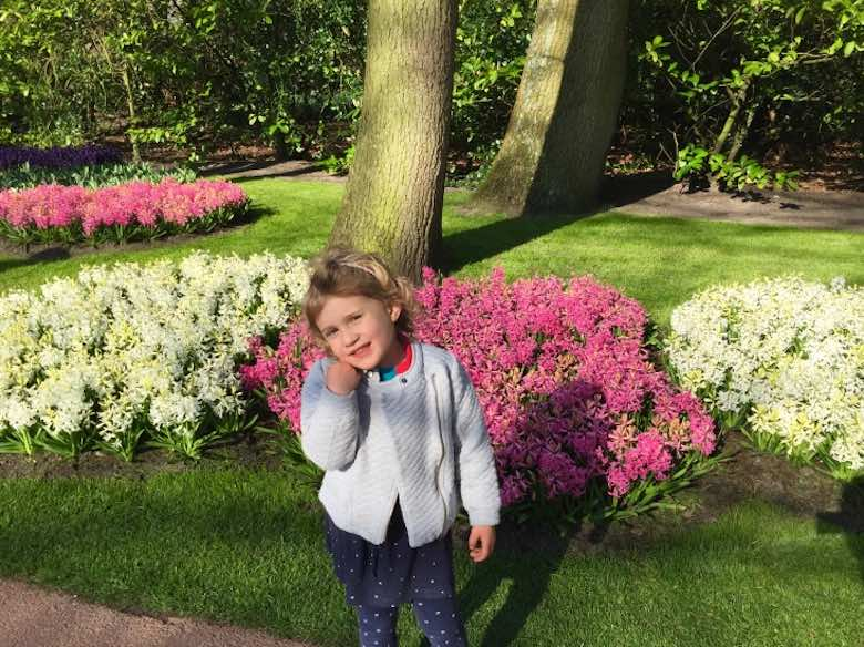 CosmopoliClan's little girl posing in front of a bed of flowers at Keukenhof Gardens in Holland