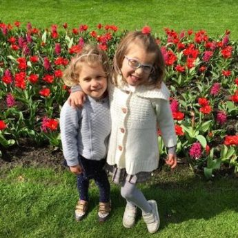 Two little sisters holding each other while posing in front of a bed of red flowers in Keukenhof Gardens in Holland