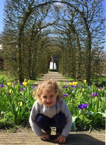 CosmopoliClan's little girl squatting in front of a bed of yellow and purple tulips in Keukenhof Gardens in Holland