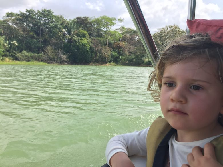 CosmopoliClan's little girl on a boat over the Chagres river in the Panama Canal, surrounded by the Gamboa rainforest