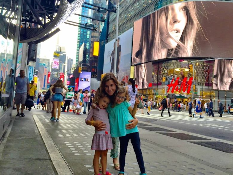 Mother and her daughters posing in front of Times Square during CosmopoliClan's NYC family adventure