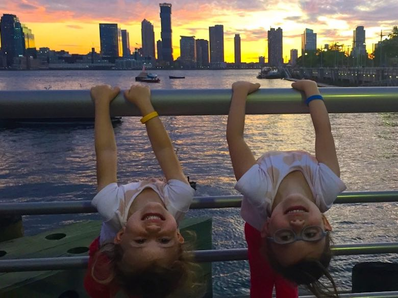 Two girls hanging over the railing at Pier 25 in TriBeCa during sunset over the Hudson River and the Jersey City skyline