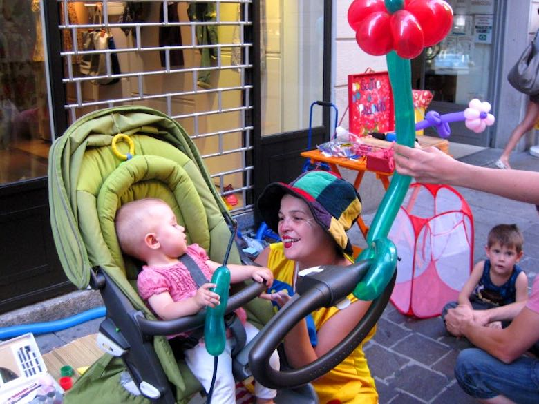 Clown making a balloon for a little baby girl in a stroller and interacting with her in the streets of Como