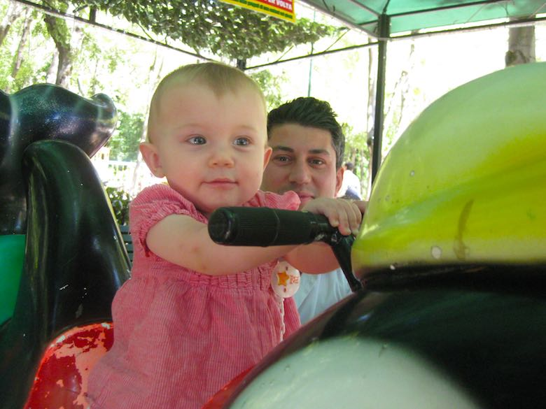 Baby girl enjoying the carrousel with daddy by her side