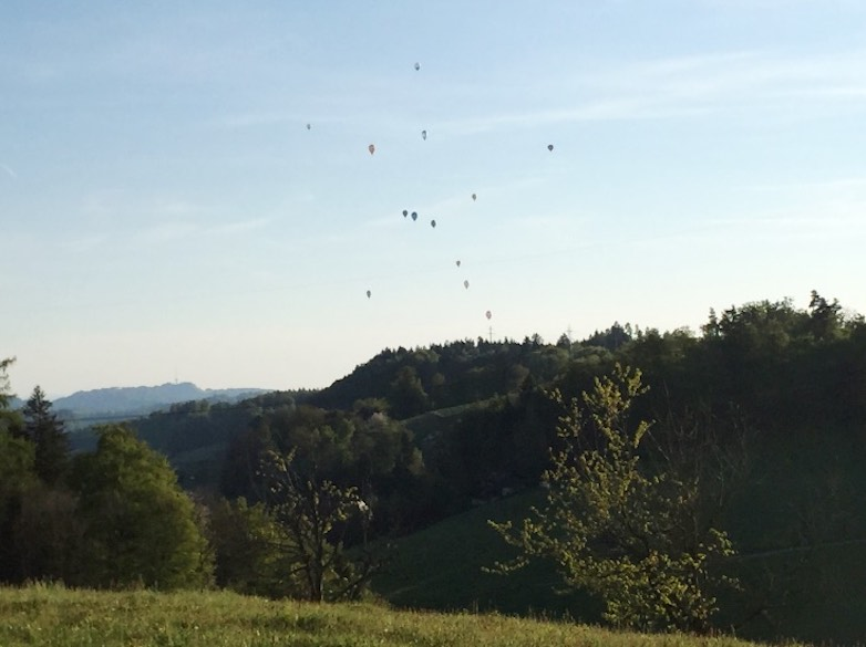 Panoramic picture of the rolling green hills of the Emmental region with dozens of hot air ballons in the sky, taken from the terrace of the Gasthof zum Hirschen in Kaltacker, Switzerland