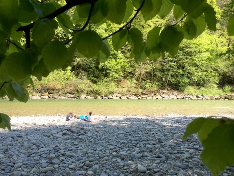 Family enjoying a picnic on the bed of the Emme river in Switzerland