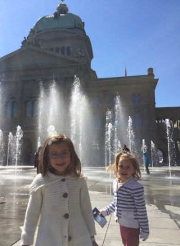 Two little girls smiling with in the background the splashing fountains and Das Bundeshaus, Federal Palace of Switzerland, against a clear blue sky