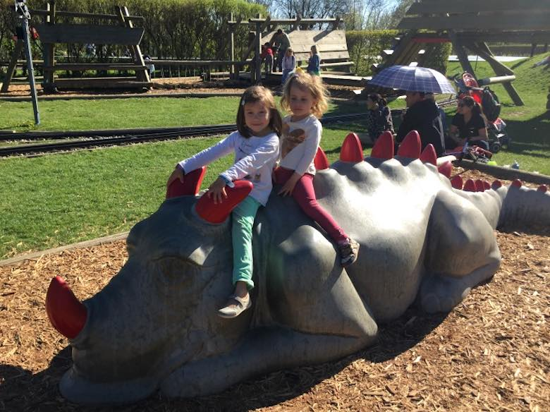 Two little girls riding a dragon at the play area on the Gurten mountain
