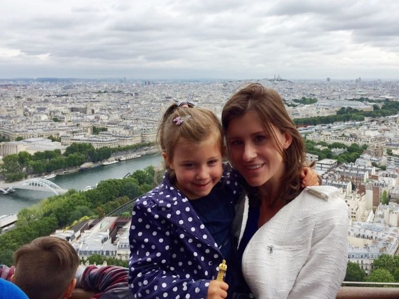 Mother and daughter posing on one of the platforms of the Eiffel tower in Paris