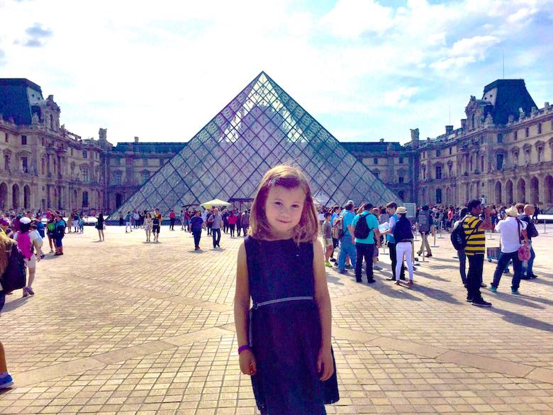 Posing in front of the glass pyramid at the Louvre in Paris