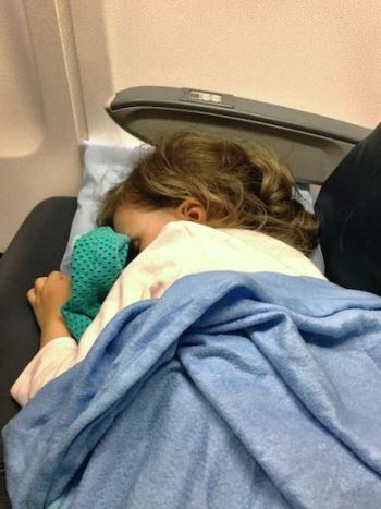 CosmopoliClan's Jade taking a nap on the plane, with her head on the pillow and covered with a blue blanket
