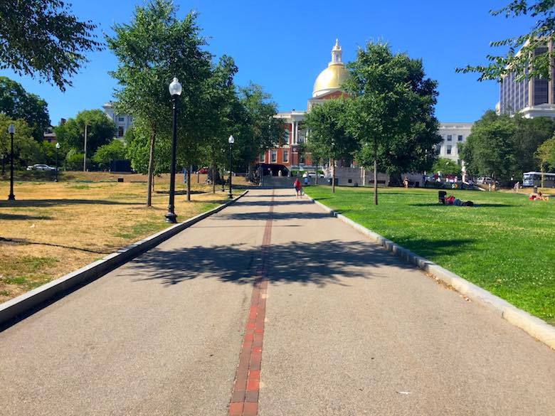 The start of the Freedom Trail in Boston Common, indicated by a red brick line and showing the golden dome of the Massachusetts State House, the starting point to learning all about Boston's heritage