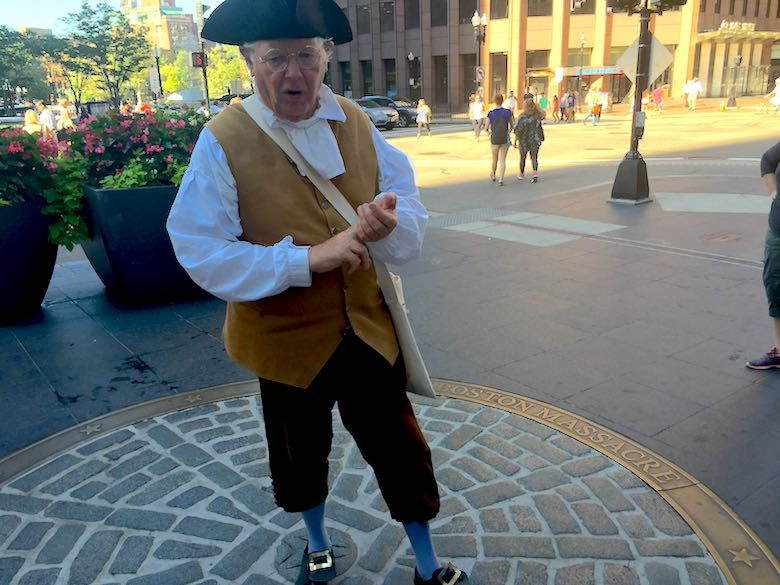A customer historical figure, representing james otis, standing on the Boston Massacre memorial during a Freedom Trail guided tour