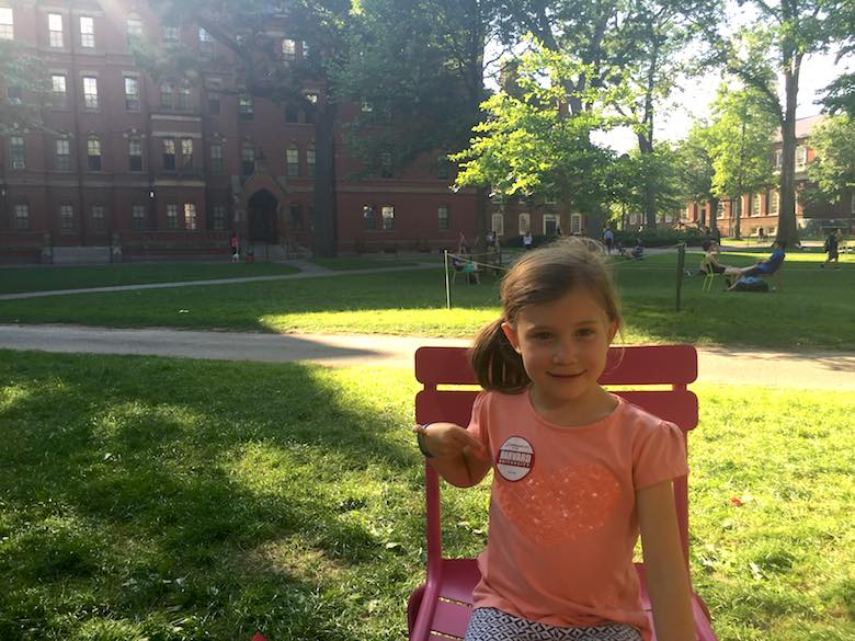 Little girl on Harvard Yard, sitting in a red chair and proudly pointing at the Harvard tour sticker on her orange t-shirt