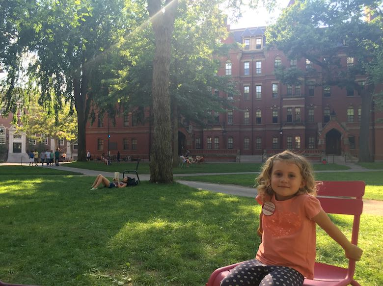 Little girl sitting in a red chair on Harvard Yard, with in the background a young woman reading a book on the grass