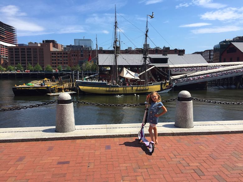 Little girl proudly posing next o her scooter in front of a restored ship at the Boston Tea Party museum, explaining Boston's heritage