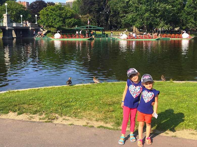 Two CosmopoliClan sisters posing in the Public Garden, one of the best spots for free summer fun in Boston, with the swan boats in the backdrop