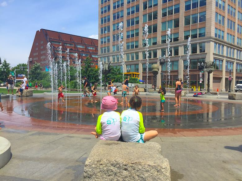 Two sisters looking out over the Rings splash fountain with playing kids in the Rose Fitzgerald Kennedy Greenway park in Boston, one of the best places for free summer fun in Boston