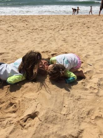 Beach fun in authentic Algarve in Portugal, picture taken on Falesia beach where the kids buried their dad in sand and kissing him on the cheeks