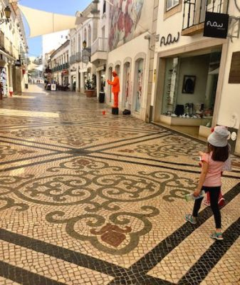 Girl walking over the mosaic tiling of a street in Faro towards a street artist
