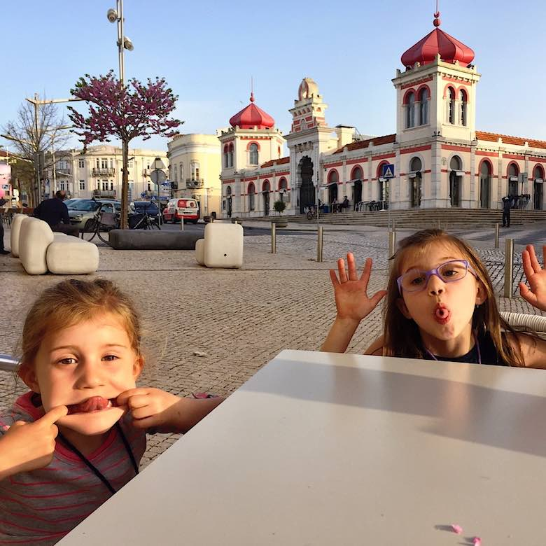 Two little girls making silly faces at a terrace in Loule in authentic Algarve with the market place building in the backdrop