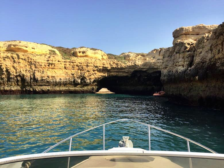 Bow of the boat facing a grotto along the stunning coastline of the authentic Algarve