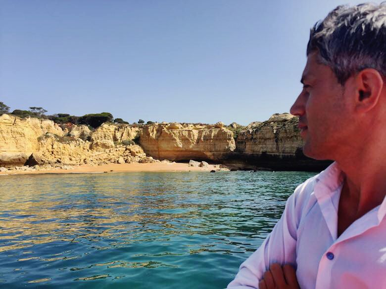 Profile of a man looking over a deserted beach along the stunning coastline of the Algarve in Portugal from a boat