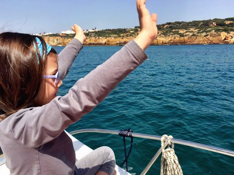 CosmopoliGirl waving from the boat to the beach seekers along the coastline of the Portuguese Algarve